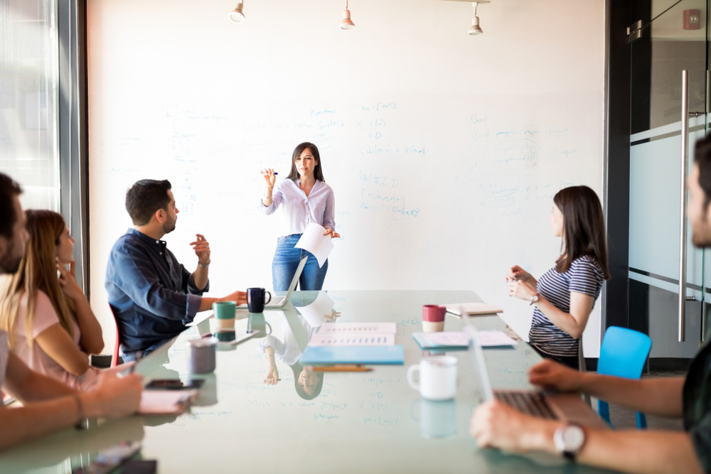 latina woman giving a presentation to a group around a table