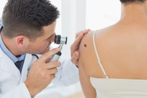Doctor examining a mole on a patient's back