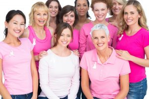 Women of all ages and ethnic backgrounds wearing pink shirts with pink cancer awareness ribbons.